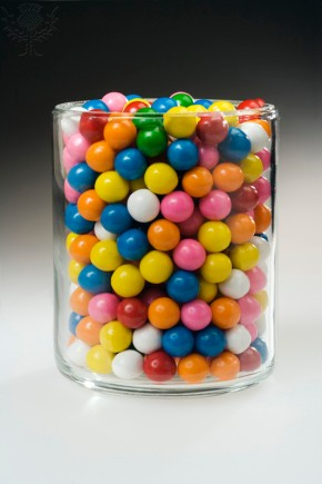 ESTIMATING A NUMBER: CANDIES IN CYLINDER Colorful Gumballs. Many candies in a clear cylindrical container to illustrate a problem in estimating the number.